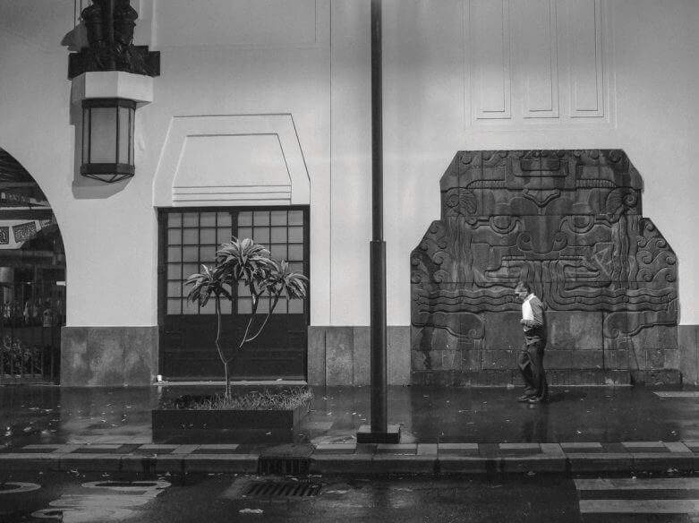 Black and white picture of a man walking on the street